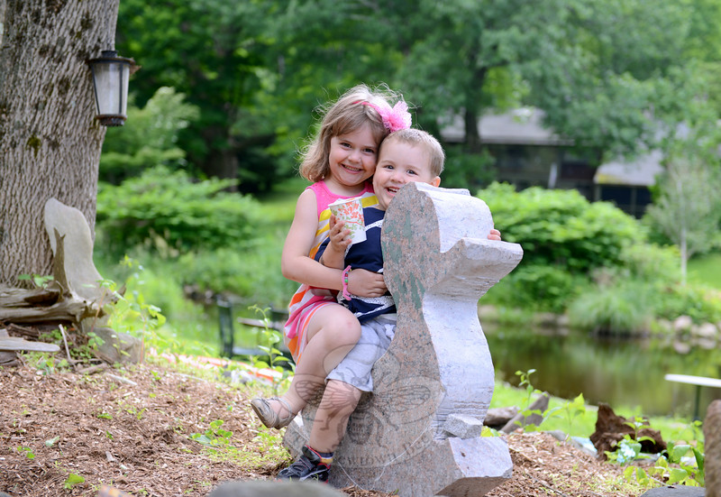June Cash and her brother Reid take a time out of their play to perch on a stone carved duck.  (Bobowick photo)