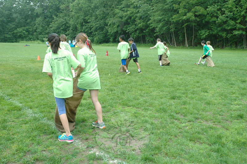 Working in teams and sharing a potato sack, students make it down around a cone and back to their classmates during Sandy Hook School's Field Day. (Hallabeck photo)
