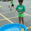 "Hanna Linden ""fished"" for rubber ducks out of a small plastic pool at one Field Day station on June 12.  (Hallabeck photo)"