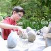 Roman Achille works with stone puzzles designed by Ethan Currier.  (Bobowick photo)