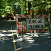 This blockade, positioned on the southbound lane of Poverty Hollow Road near the entrance to the Centennial Watershed State Forest parking lot, makes it clear that the nearby bridge that crosses over the Aspetuck River is closed. In fact, the bridge is missing, having been removed by construction workers who will replace it with a modern span. The river is being channeled through culverts during the construction process. While construction is under way, the several hundred motorists who normally travel through the area daily are being detoured to parallel roads. The new bridge is scheduled to be in service by mid-August.   (Gorosko photo)