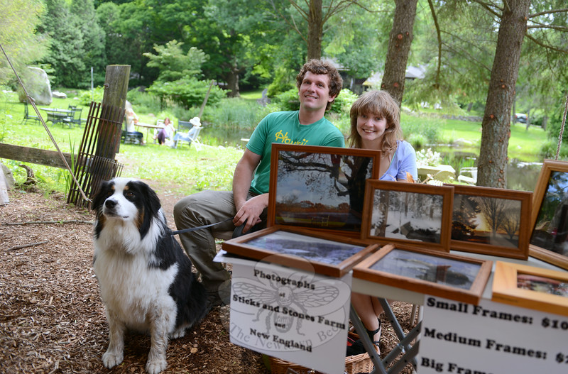 Shawn and Luise Gleason and their dog relax in the shade where they set up samples of their framed photography.  (Bobowick photo)