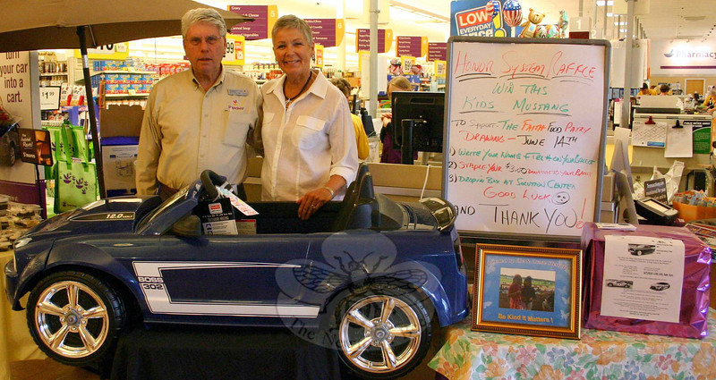 Stop & Shop Store Manager Rich Marcuccio and FAITH Food Pantry Volunteer Barb Krell stand behind a Fisher-Price Power Wheels Ford Mustang that is being raffled to raise funds for the Sandy Hook-based food pantry. Mr Marcuccio is also organizing a car show that will also serve, on June 14, as a fundraiser for the food pantry. (Hicks photo)