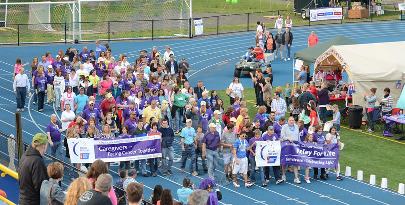 More than 100 local cancer survivors and caregivers round the final bend at Newtown High School's Blue & Gold Stadium May 31 during the opening lap of the 10th Relay For Life. (Voket photo)