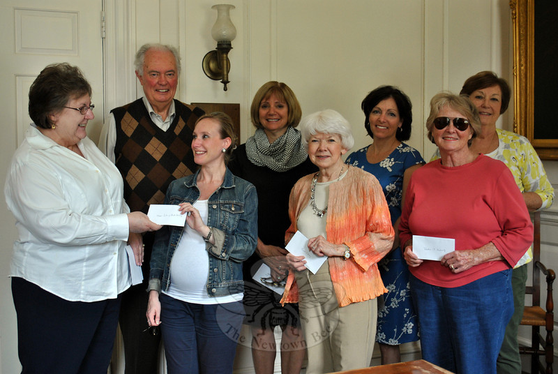 Samantha Flynn, development director for the Women's Center of Greater Danbury, second from left, front, accepts a check from Newtown Woman's Cub, GFWC, Inc President Nina Morrisson, Friday, May 30. The Newtown Woman's Club presented checks to support Newtown Ambulance Association, Regional Hospice and Home Care of Western Connecticut, Newtown Meals On Wheels (MOW), the combined fire companies of Newtown, the Labor Day Parade Committee, Newtown Scholarship Association, WestConn Fresh Start Scholarship (supporting women 30 years and older enrolled in a full degree program), Kevin's Community Center (KCC), C.H. Booth Library, and the Women's Center, on Friday. Representing their organizations, in addition to Ms Flynn, are Beryl Harrison (Booth Library), and Shirley Ferris (Fresh Start); back row, from left, Brian Amey (Labor Day Parade Committee), Stephanie Gaston (Scholarship Association), Lucy Liponi (KCC), and Marg Studley (Hospice and MOW). The Newtown Woman's Club has donated $8,700 to various local and area organizations so far this year. (Crevier photo)