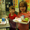 Head O' Meadow Elementary School students Eric Clarke, left, and Emma Hall added frozen yogurt cups to their lunch on Thursday, March 6. (Hallabeck photo)