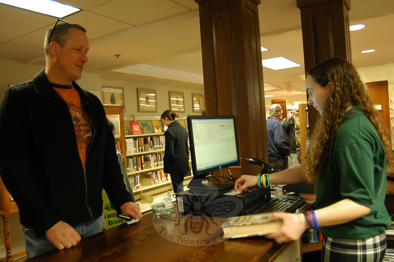 John Gonski, left, signed a book out at C. H. Booth Library on Saturday, with the help of library staff member Ryan Murphy. (Hallabeck photo)