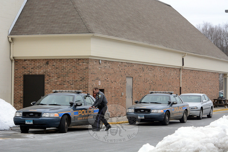 A town police officer enters a patrol car parked on the south side of the Stop & Shop supermarket at Sand Hill Plaza at 228 South Main Street in Botsford after participating in a police investigation into a telephone scam on the afternoon of Friday, March 7.  Another marked police car and a police detective's car are parked nearby. (Gorosko photo)