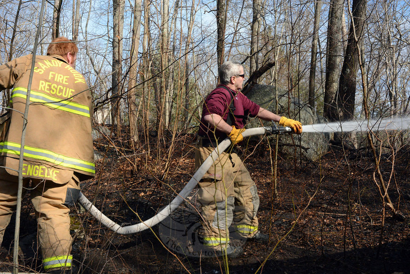 Botsford and Sandy Hook firefighters joined forces on the windy afternoon on Wednesday, March 26, to put out multiple brush fires along High Rock Road. Shown handling a fire hose alongside High Rock Road are two Sandy Hook volunteers, Engineer Brian Engelke, left, and firefighter Bob Nute. (Gorosko photo)