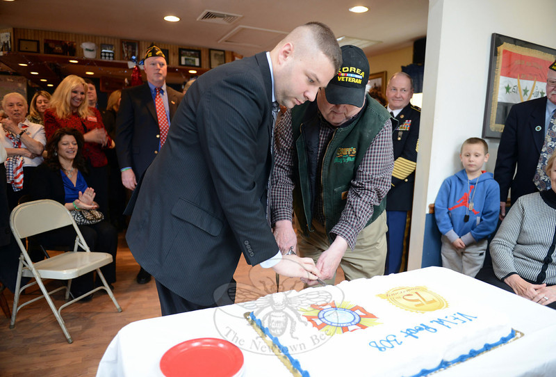 Veterans, their families, and several dignitaries gathered at VFW Post 308 on Freedom Defenders Way March 2 to mark the 75th anniversary of the post. Senior Post member George Lockwood, right, shares the first cut into an anniversary cake with younger member veteran Carl Bergquist during the post's celebration of the milestone. (Bobowick photo)