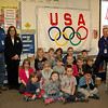 Head O' Meadow security guard Mike Kaylor, left, shared a flag his father earned from participating in the 1936 Olympic games with students in Carol Howard's first grade class on Wednesday, February 26. Ms Howard, right, and school Principal Barbara Gasparine, second from left, also stood with the students for a picture with the flag. (Hallabeck photo)