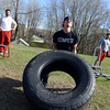 David Bray, left, demonstrates an exercise stool while Cole Depuy works out with a tire. To the right, John Grimaldi gets ready to push another piece of exercise equipment. The men are among the instructors available for boot camp participants at Total Performance Sports & Fitness. (Bobowick photo)