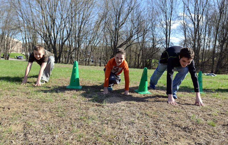 From left are brothers Ryder, 9, Vinnie, 10, and Jake Wilson, 15, getting ready to race on an outdoor field, which is available for boot camp activities at Total Performance Sports & Fitness. The fitness facility on Pecks Lane is offering a special series of boot camp classes through June 29. All proceeds from the classes will be given to Hawley School teacher Stephanie Dunshee, to help pay for ongoing medical expenses. (Bobowick photo)