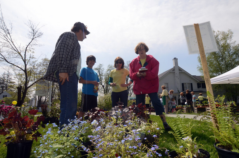 The Town and Country Garden Club of Newtown held its annual plant and flower sale at The Inn at Newtown Saturday, May 10. Volunteers mixed with interested supporters, many of whom walked away with arms or wagons full of hand tended flora for their own properties. Event organizer Mary Weiner, right, and volunteer Teri Doern spent a few minutes chatting with Jack Nahmias and his son Jon about the variety of plants available for their yard. (Voket photo)