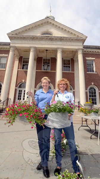 After an evening of rain showers, it was turning into a lovely morning Saturday, May 10, as Monika Kurrle-Taylor, right, and Carolyn Mitchel, left, took up positions at Edmond Town Hall volunteering for the Newtown Junior Women's Club for the group's annual pre-Mother's Day flower sale.  (Voket photo)