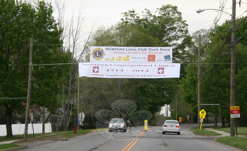 Banners for The Great Pootatuck Duck Race & Town Festival have been hung in Sandy Hook Center and, shown here, above Queen Street near its intersection with Lorraine Drive. The new banners advertise the upcoming event, while also promoting the new partnership between Newtown Lions Club and SHOP. (Hicks photo)