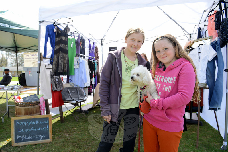 Lily Moreno Sheridan, left, and Diana Wipf spend a moment cuddling Coco as they peruse the booths. (Bobowick photo)