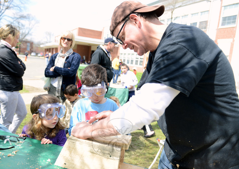 Ivy and Noah Masotta wear their safety goggles as Ben Toby helps them assemble a bird house.	(Bobowick photo)