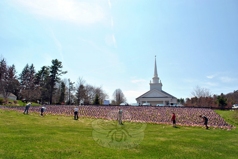 Volunteers began placing 6,800 flags honoring American lives lost in wars in Afghanistan and Iraq, Friday morning, April 25, on the sloping lawn of the Newtown Congregational Church at 14 West Street. The flags will remain in place for three weeks before returning to the Somers (Conn.) Congregational Church, where members there first placed more than 2,000 flags, October 23, 2005. The Field of Flags will be retired after its final display in Somers, after having been displayed at 70 churches, mostly on the East Coast. The Fields of Flags appeared at Newtown Congregational Church one time previously, in 2009. At that time, casualties numbered 4,981. (Crevier photo)