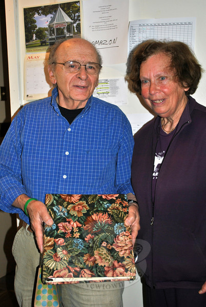 Pete and Julie Stern hold a book of memories compiled for them by members of the Friends of the C.H. Booth Library. The Sterns were honored at a gathering Monday morning, May 19. (Crevier photo)