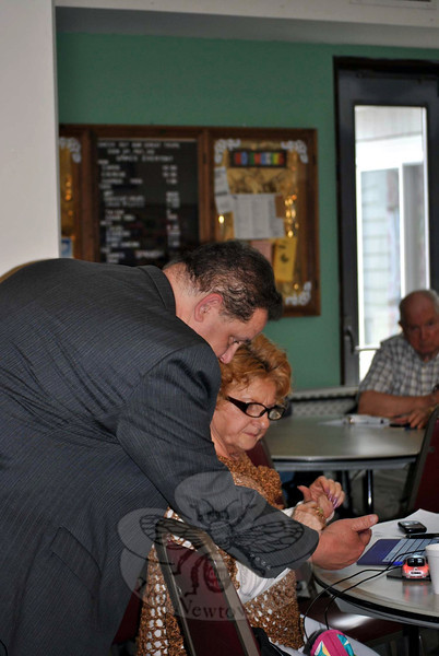 State Representative Mitch Bolinsky gives Dottie Dellapiano a glimpse of what a smartphone can do, and answers her questions. (Crevier photo)