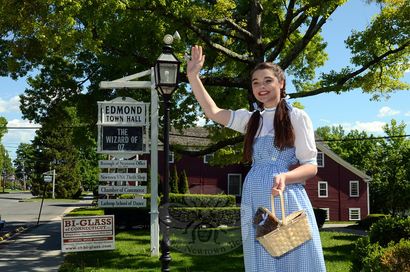"Kirsten Liniger, dressed as Dorothy and carting ""Toto"" in her basket, waves to passersby before Sunday's screening of The Wizard of Oz at the Edmond Town Hall Theatre. The classic film marked the debut of the Sunday Cinema Series organized by Newtown Cultural Arts Commission and the town hall Board of Managers. The next screening in the series — a monthly event through the end of the year that will continue to celebrate films of 1939 — is June 29 with Ninotchka featuring Greta Garbo along with a Laurel & Hardy film Flying Deuces. (Voket photo)"