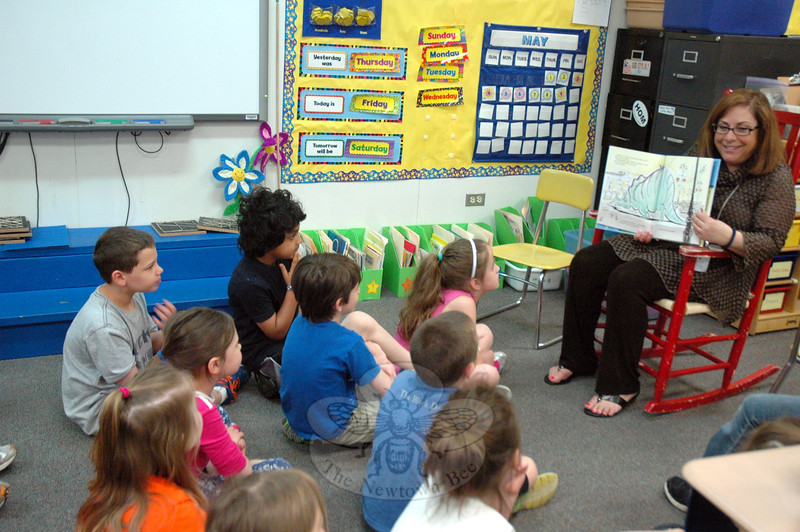 A number of guests visited Head O' Meadow Elementary School on Monday, May 12, to read to students. In different classrooms, Head O' Meadow students huddled around the visitors to hear them read from books, like in one classroom where Head O' Meadow Principal Barbara Gasparine read When Dinosaurs Came with Everything by Elise Broach to students. (Hallabeck photo)