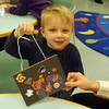 Nicholas Wengart shows off his finished bag, decorated with stickers, created during the Drop-In Halloween Craft event at C. H. Booth Library. (Silber photo)