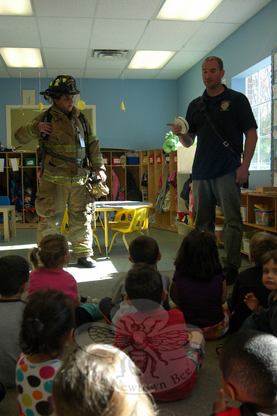 """""""Hi, firefighter,"""" one child at Misty Morning said as a Newtown Hook & Ladder Co. #1 truck pulled into the parking lot on Friday, October 18. Newtown Hook & Ladder Fire Chief Jason Rivera, right, and member Ricky Camejo later gave a presentation in one of the preschool's classrooms about fire safety and prevention. The visit was one during the week of October 14 to 18 when Misty Morning Children's Center learned about community helpers and the role they play in our community. Representatives of the Newtown Ambulance and the Danbury Police Department also visited with the children. (Hallabeck photo)"""
