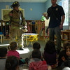 """Hi, firefighter,"" one child at Misty Morning said as a Newtown Hook & Ladder Co. #1 truck pulled into the parking lot on Friday, October 18. Newtown Hook & Ladder Fire Chief Jason Rivera, right, and member Ricky Camejo later gave a presentation in one of the preschool's classrooms about fire safety and prevention. The visit was one during the week of October 14 to 18 when Misty Morning Children's Center learned about community helpers and the role they play in our community. Representatives of the Newtown Ambulance and the Danbury Police Department also visited with the children. (Hallabeck photo)"