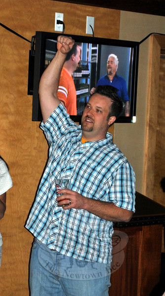 Chef Plum raises an arm in triumph, Sunday evening, as friends hear him pronounced winner of Guy's Grocery Games, at the end of the show's second episode. A scene from the show appears in the background. (Crevier photo)