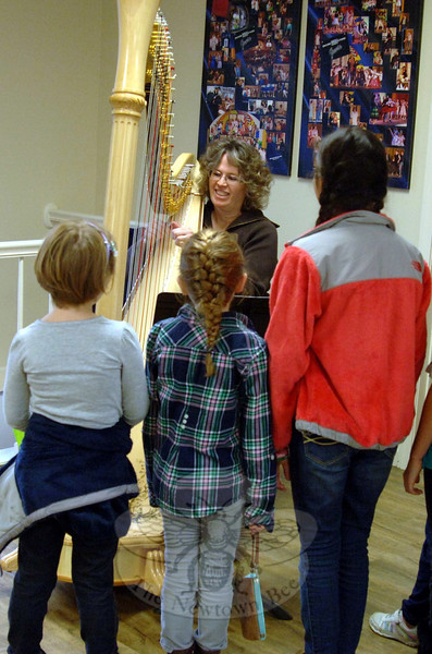 Betsy Wellington leads students through a song as she plays the harp during an open house for Sabrina's Encore Productions LLC. (Bobowick photo)