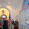 "State Representative DebraLee Hovey and Selectman Will Rodgers look on as First Selectman Pat Llodra speaks during unveiling ceremonies for a new Armed Forces mural at the Newtown Municipal Center November 9. Mrs Llodra remarked that the work of local artist David Merrill ""amazed, impressed, honored, and humbled"" those gathered to see it for the first time. (Voket photo)"