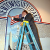 Artist David Merrill removes the last speck of masking paper that covered a memorial mural he created for the Newtown Municipal Center to honor residents who have served in the Armed Forces since 1971. The mural was unveiled during a brief ceremony Saturday, November 9. (Voket photo)