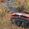 A sedan that was involved in a one-car accident during rainy, wet conditions at about 1:39 pm on November 7, came to rest with its rear end pointed downward and its undercarriage positioned verti-cally against a drainage structure off the right road shoulder of the Exit 10 on-ramp for eastbound Interstate 84. State police said that motorist Laura Collins, 23, of Waterbury was driving a 2007 Pontiac G-6 on the wet on-ramp when the vehicle went out of control and then slid through three strands of guardcabling before rolling backward down an adjacent embankment. The auto came to rest in the area where Tom's Brook is discharged from a culvert. State police said that Collins received a possible injury, but was not transported by ambulance. Newtown Volunteer Ambulance Corps members and Sandy Hook firefighters responded to the accident. State police said they issued Collins an infrac-tion for traveling too fast for conditions. Many accidents occur on that on-ramp during slick conditions. (Gorosko photo)
