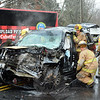 As steam rose upward from a smashed radiator, Hook & Ladder firefighters, aided by firefighters from Sandy Hook and Botsford, worked to extricate a local youth from a SUV that was involved in a head-on crash with a coach bus, seen at rear, at Fairfield Hills. The incident occurred about 2:11 pm on November 7 on Wasserman Way, just east of its intersection with Mile Hill Road South. The youth received relatively minor injuries in the accident, which closed down a section of Wasserman Way until the wreckage could be cleared away. (Gorosko photo)