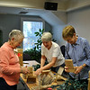 From left, Darlene Jackson, Carol Smiley, and Chris Reed look over the boxes of multicolored LED lights to insert into strings that will decorate the two trees in Ram Pasture this holiday season. The three women were among 12 volunteers working Monday morning, November 18, to replace 1,000 clear bulbs with the LED lights donated by the Newtown Energy Commission, adding to the 1,000 lights re-placed last year. The strings of wires for the lights were provided by the Newtown Chamber of Commerce, the sponsor of the Ram Pasture tree lighting for the past 29 years. (Crevier photo)