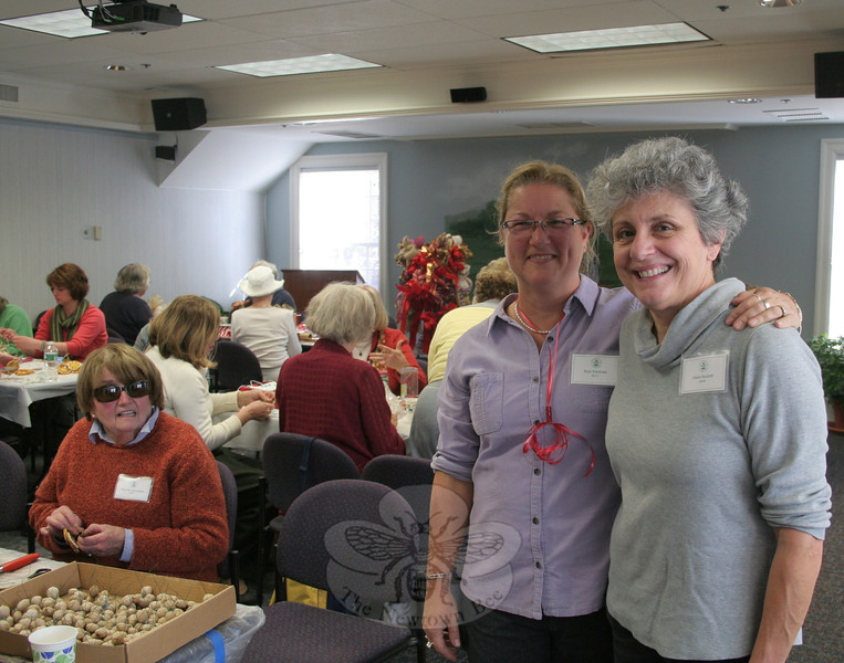 Kim Verdries, left, and Diana Baumer are the co-chairs of this year's Garden Club of Newtown Christmas Greens Sale. The women organized a work session for club members this week, the first of at least three that will be held before this year's event returns to Newtown Meeting House on December 7. Looking up from one of the work stations is longtime club member Maureen McLachlan. (Hicks photo)
