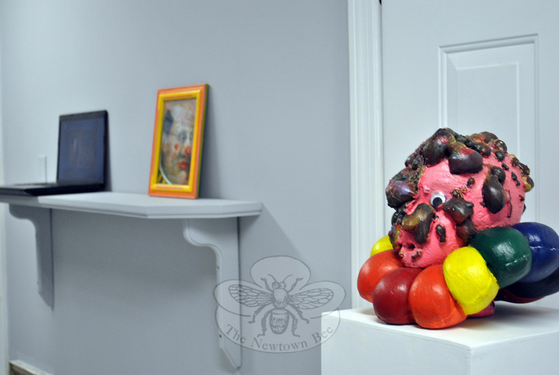 """""""Fun Dump"""" is a clown sculpture by the painter and sculptor Michael Dassle, on display as part of """"Purpose,"""" the inaugural exhibition at Migrant Salon. The oil painting """"Clown,"""" by Anthony Palocci, Jr, sits on the shelf in the background, along with """"Painter's Dance,"""" a performance piece video by Holyoke artist Suzy Evans. (Crevier photo)"""