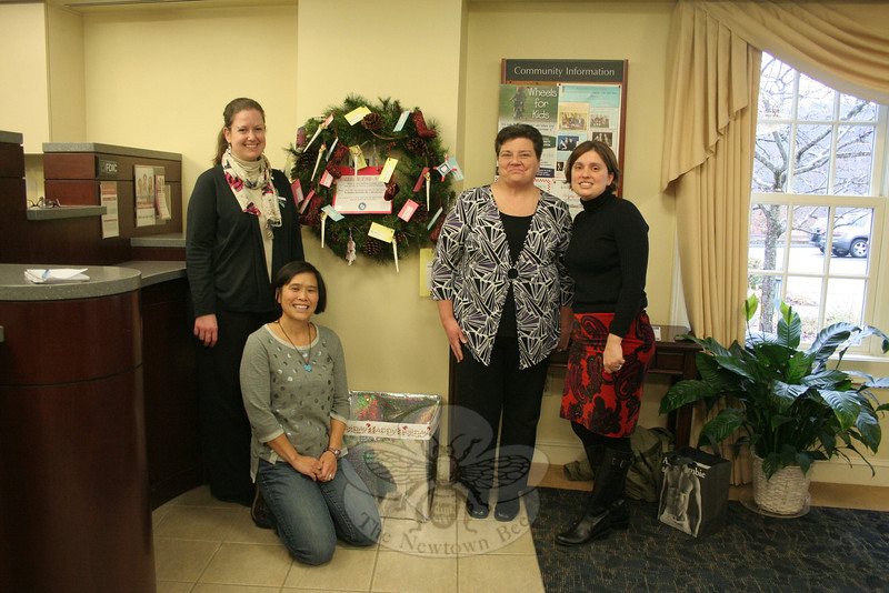 Newtown Savings Bank Teller Lauren Kochanov, left; NJWC member Meri Jitsukawa, kneeling; and NSB Call Center Supervisor Marlene Husvar and Closing Department Manager Stephanie Griffin put the Tag-A-Gift wreath into place at Newtown Savings Bank's main branch on November 22. The bank is one of five locations in town hosting trees and wreaths with tags that feature gift wishes from residents who need a hand this holiday season.   (Hicks photo)