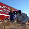 Sandy Hook Firefighter Pete Barresi got a helping hand from Boy Scout Evan Nikolis from Den 6, Pack 170, during the Fill The Fire Truck Food Drive.  (Voket photo)