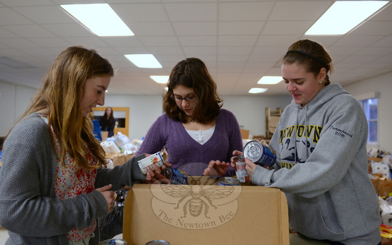Students Julia Faxon and WIN-terns, a junior WIN student group, Sophie Kennen and Amanda Tramposch worked to place canned foods in boxes.   (Bobowick photo)