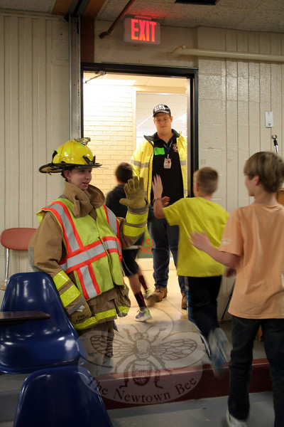 Firefighter Andy DeWolfe, kneeling, gave high fives to students as they left each program. Standing in the doorway is Sandy Hook Junior Corps member Sam Celentano, also greeting students.