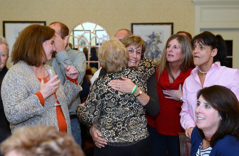 Both reelected Tuesday night, First Selectman Pat Llodra (back to camera) and Legislative Council member Mary Ann Jacob share a hug. Around them are Board of Education Chairman Debbie Leidlein left, BOE member Kathy Hamilton, right, and supporter Judy Thomas, far right.  (Bobowick photo)