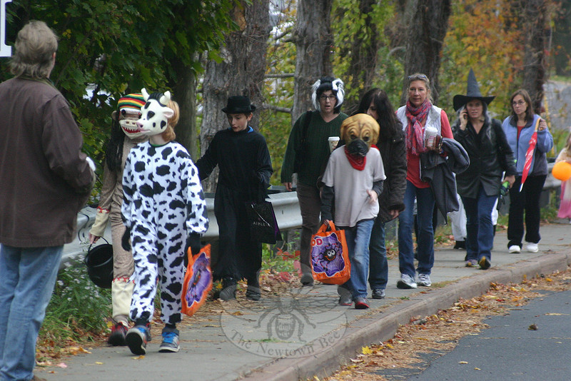 Longtime Main Street resident Lucy Sullivan prepared for 3,300 Halloween visitors last week, but tells The Newtown Bee she did not go through all of her candy this year. Many of her neighbors prepared for 2,000 visitors and did run out, around 7 pm, after trick or treaters descended upon Main Street for the first full Halloween celebration since 2010. Halloween in town had been all but cancelled in 2011 after Winter Storm Alfred dropped heavy, wet snow across the region and created dangerous settings for the autumn holiday. Last year it was Superstorm Sandy that diminished the season's spirits, causing town officials to ask residents to wait until November 4 for trick or treating. Last week costumed residents of all ages returned for the seasonal fun, including this crew seen heading up Church Hill Road around 5 pm. After speaking with some of her neighbors, Mrs Sullivan estimates approximately 2,500 guests visited some of the Main Street homes this year. (Hicks photo)
