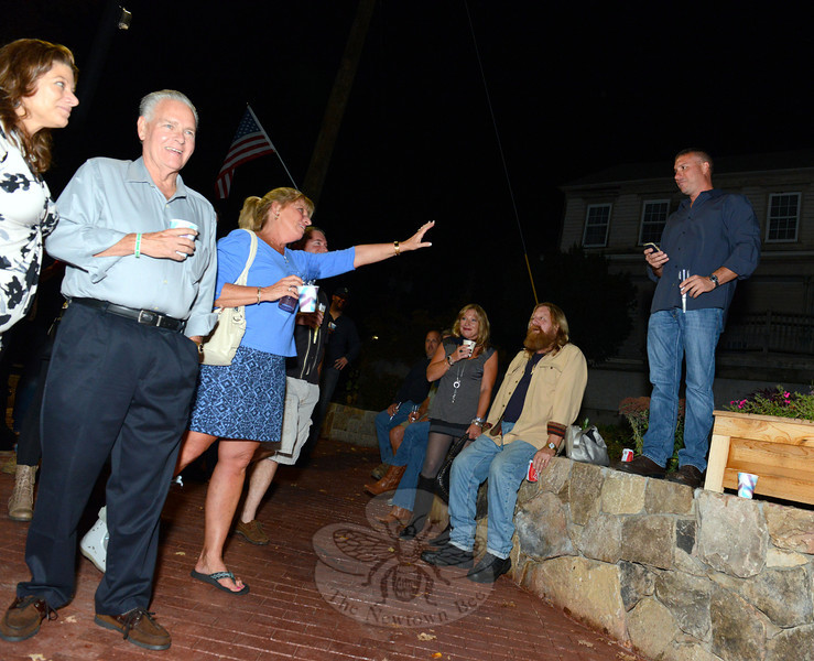 Meribeth Hemingway reaches a hand toward Rob Manna as he offers a few words to mark the completion of the Sandy Hook Streetscape Phase II Friday, October 3. To the left are Fire Chief Bill Halstead and Town Clerk Debbie Aurelia Halstead. (Bobowick photo)