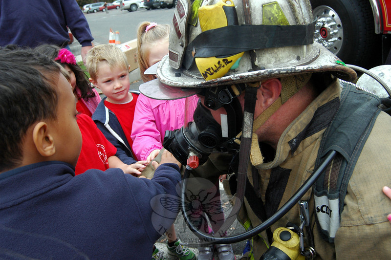 Newtown Hook & Ladder Co. #1's Joe Miller let St Rose of Lima School kindergarten and first grade students touch his suit on Friday, October 11, during a fire safety demonstration and to help the children become accustomed to a firefighter's presence. (Hallabeck photo)