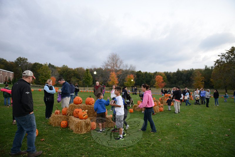 """The grinning and grimacing faces of hundreds of pumpkins lit up the early evening darkness at Fairfield Hills Saturday, October 12, at the first Newtown Pumpkin Festival. The event drew a large crowd of pumpkin fans.  Story available here, <a href=""""http://www.newtownbee.com/news/news/2013/10/17/pumpkin-festival-sparkles-fairfield-hills/169375"""">http://www.newtownbee.com/news/news/2013/10/17/pumpkin-festival-sparkles-fairfield-hills/169375</a> . (Bobowick photo)"""