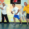 On Friday, October 18, during its fifth anniversary celebration, the NYA staff unveiled muralist Nichole Blackburn's donation of artwork covering the recreation and community facility's walls. Coaches and staff at the NYA mimic the mural's poses. From left are Robert Frangione, Jeff Tousignant, and Eric Lambert. (Bobowick photo)