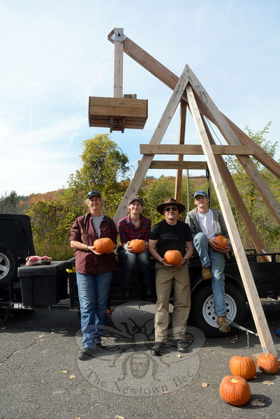 Members of the Michaud family of Sandy Hook, from left, Catherine, Nancy, Marc, and Alex, display some compact pumpkins that were hurled by the trebuchet, background, a medieval-era siege engine which they demonstrated at the 4th Annual Great Pumpkin Race.  (Gorosko photo)
